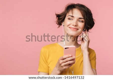photo of young woman 20s listening to music on smartphone via ea stock photo © deandrobot
