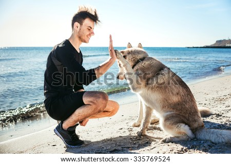 Happy young couple walking with big dog on the beach in summer stock photo © ElenaBatkova