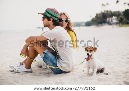 young stylish hipster couple in love walking playing dog puppy in tropical beach white sand cool o stock photo © elenabatkova