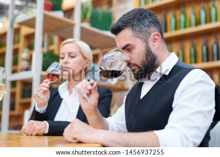 Young bearded sommelier in formalwear smelling new sort of red wine Stock photo © pressmaster