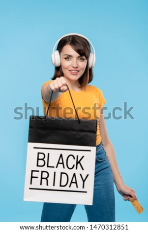 Happy young shopaholic giving paperbag with black friday purchase Stock photo © pressmaster