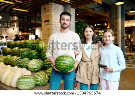Young casual family of three buying ripe watermelon in modern supermarket Stock photo © pressmaster
