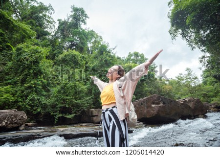 Young woman standing in front of waterfall with her hands raised. Female tourist with her arms outst Stock photo © galitskaya