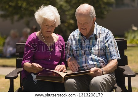 Front view of senior woman looking at photo album while senior couple using digital tablet and a sen Stock photo © wavebreak_media