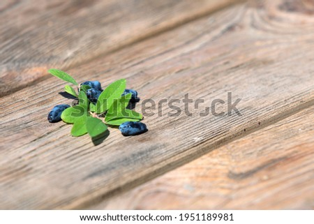 Fresh honeysuckle blue berry fruits with leaf on a wooden background Stock photo © galitskaya