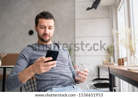 Young restful man having glass of water and scrolling or messaging in smartphone Stock photo © pressmaster