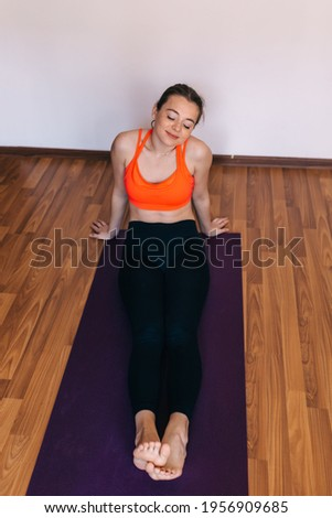 Stock photo: Young sportswoman tired after hard training sitting on mat by climbing walls