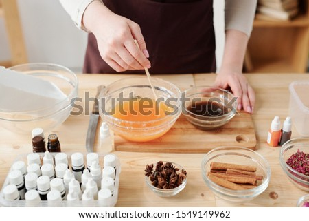 Craftswoman mixing liquid soap mass with orange essential oil in bowl Stock photo © pressmaster