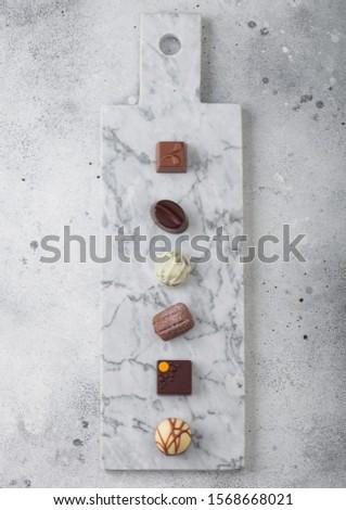 Luxury Chocolate candies selection on light marbel board. White, dark and milk chocolate assortment. Stock photo © DenisMArt