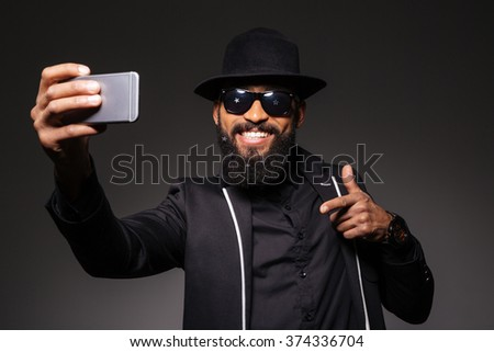 Happy young elegant man with smartphone making selfie on couch in night club Stock photo © pressmaster