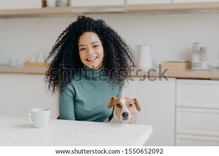 Pretty young lady with Afro hairstyle plays with dog, wears comfortable jumper, drinks coffee or tea Stock photo © vkstudio