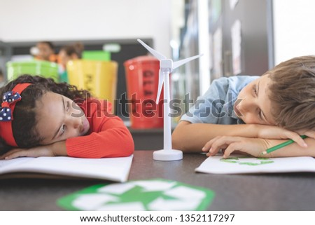 Front view of two tired school kids observing a windmill mockup between them in classroom against tr Stock photo © wavebreak_media