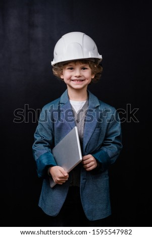 Cute little boy in hardhat and formalwear holding folded laptop in isolation Stock photo © pressmaster
