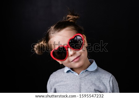 Cute girl in sunglasses with heartshaped lens standing in front of camera Stock photo © pressmaster