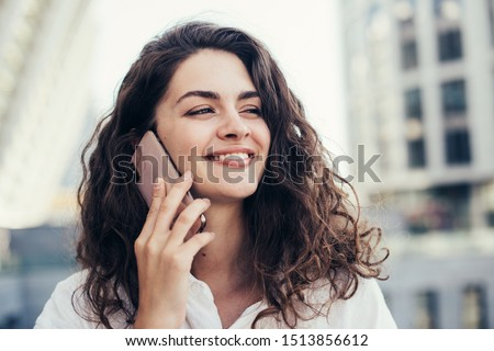 Photo of attractive young woman with dark straight hair, smiles happily, dressed in denim shirt, pos Stock photo © vkstudio