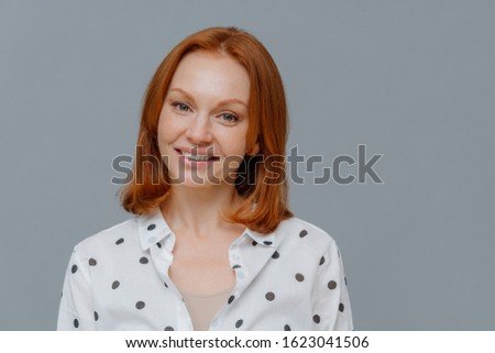 Elegant redhead woman looks at camera with gentle toothy smile, has healthy freckled skin, happy to  Stock photo © vkstudio