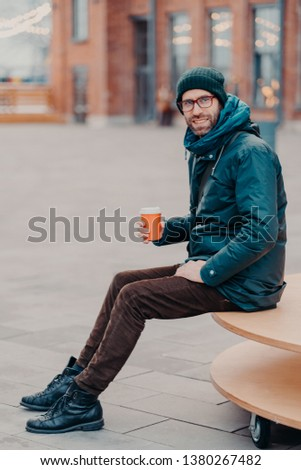Vertical shot of handsome bearded man dressed in street apparel, drink coffee to go, poses in urban  Stock photo © vkstudio