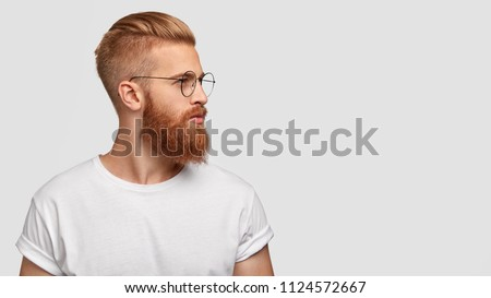 Portrait of attractive young man with thick beard and mustache looks with delighted expression, has  Stock photo © vkstudio
