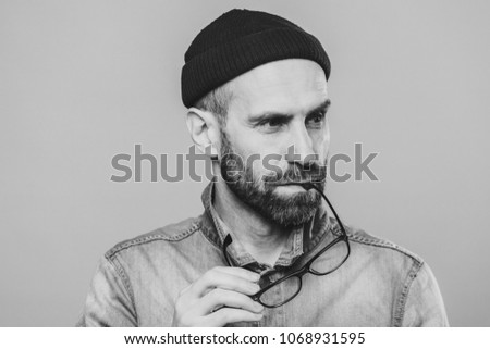 Portrait of pensive bearded man takes off glasses, wears denim stylish jacket and hat, isolated over Stock photo © vkstudio