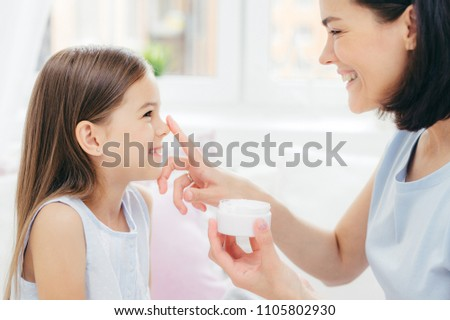 Close up shot of pretty cheerful female recieves beauty procedure from affectionate mother. Attracti Stock photo © vkstudio