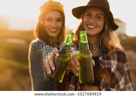 Happy young women drinks cider from the bottle by the convertibl Stock photo © boggy