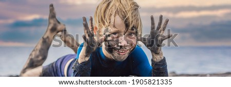 Black Friday concept. Smiling boy with dirty Black face sitting and playing on black sand sea beach  Stock photo © galitskaya