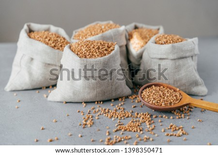 Husbandry concept. Raw buckwheat in sacks, wooden spoon near, splited cereals, isolated over grey ba Stock photo © vkstudio
