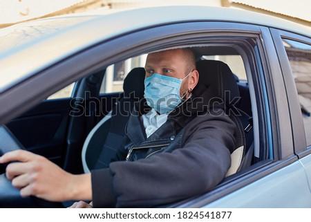 Man with protective mask adriving a car by Coronavirus pandemic quarantine Stock photo © Illia