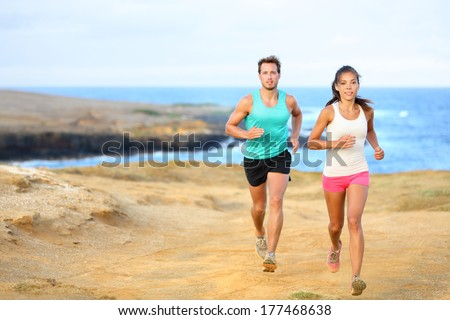 Two fitness athletes running together on beach. People from behind jogging away barefoot on sand on  Stock photo © Maridav