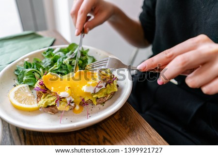Restaurant breakfast brunch avocado toast with eggs woman eating plate at cafe. Two meals couple enj Stock photo © Maridav