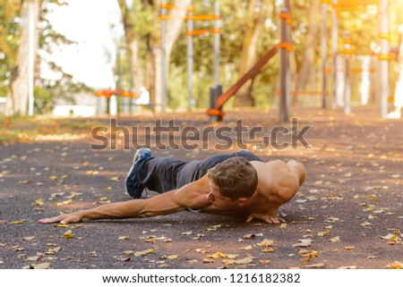 Full length of young man full of attitude doing pushups on grass Stock photo © HASLOO