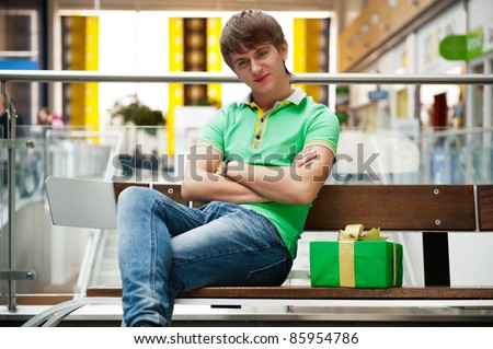 Portrait of young man inside shopping mall sitting relaxed on co Stock photo © HASLOO