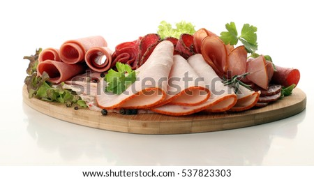 Cutting sausage and cured meat with a parsley on the white plate Stock photo © kayros