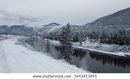 Blue water valley cuts through green mountains with snow patches Stock photo © Klodien