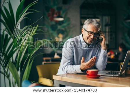 Grey haired man drinking coffee and speaking on mobile telephone stock photo © photography33