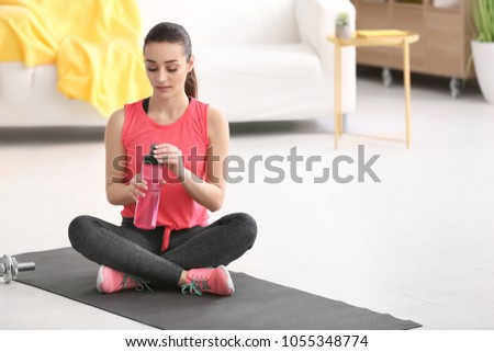 portrait of young woman drinking water at gym after doing exerci stock photo © hasloo
