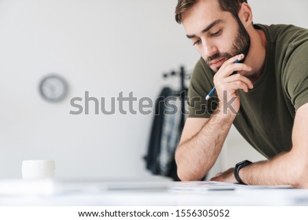 Portrait of a business man reading documents while leaning on th Stock photo © HASLOO