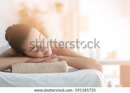 young woman relaxing on massage table in health spa with burning stock photo © hasloo