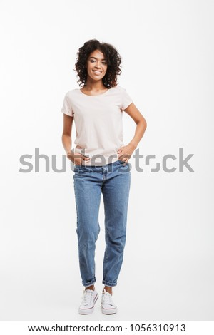 Full-length portrait of a young smiling woman in casual dress on gray background Stock photo © deandrobot