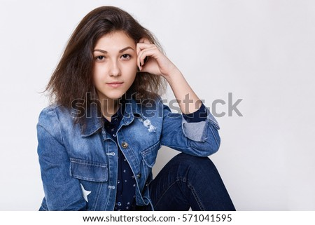 Studio shot of a thoughtful woman with her knee up on a office chair over gray background Stock photo © deandrobot