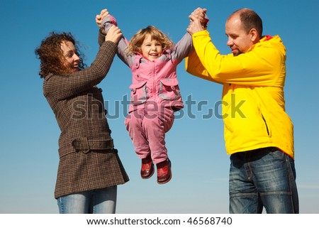 Happy girl shakes on hands at parents against blue sky, in solar autumn day. Everyone looks into cam Stock photo © Paha_L