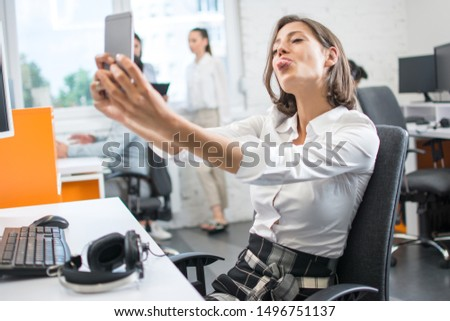 cute joyful girl showing tongue and making selfie using tablet stock photo © deandrobot