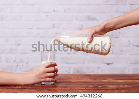 Woman hands pouring milk from bottle into glass on windowsill Stock photo © deandrobot