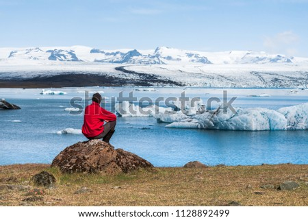 Tourist in a red jacket sits on the shores of the glacial lagoon Stock photo © Kotenko