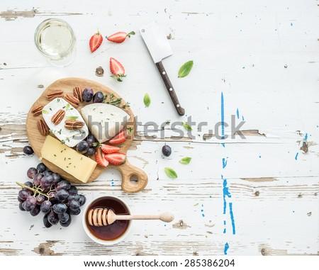 Glass with white wine, grape, cheese, over rustic wooden backgro Stock photo © Yatsenko