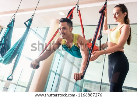 cheerful young man practicing flying yoga helped by his beautifu stock photo © kzenon