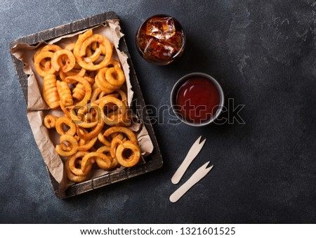 Curly fries fast food snack in red plastic tray with glass of cola on stone kitchen background. Unhe Stock photo © DenisMArt