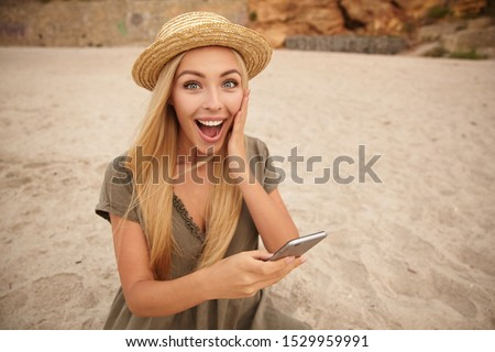 Image of pretty woman 20s wearing casual clothing holding fan of Stock photo © deandrobot