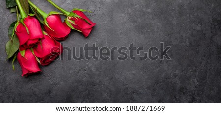 Gift box on black stone table. Romantic holiday background with rose petals Stock photo © dash