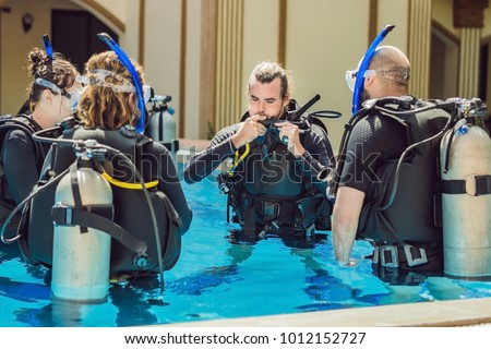Stock photo: Diving instructor and students. Instructor teaches students to dive